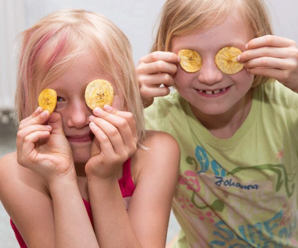 """Kinder mit getrockneten Bananenscheiben vor den Augen, Bildungsprojekt """"Kakao & Banane"""""""