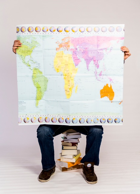 Person sitzt auf Bücherstapel und zeigt die Weltkarte hoch