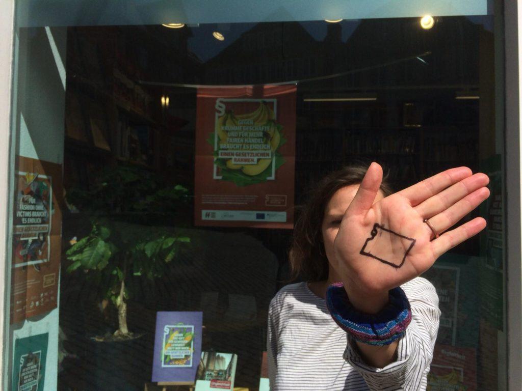 """Frau demonstriert für Lieferkettengesetzt (Logo auf die Hand gemalt), Bildungsprojekt """"Unternehmensverantwortung entlang globaler Lieferketten"""""""
