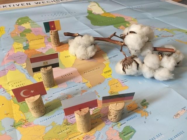 """Weltkarte mit Baumwollpflanze und Länderkennzeichungen (Flaggen), Bildungsprojekt """"Die Weltreise einer Jeans"""""""