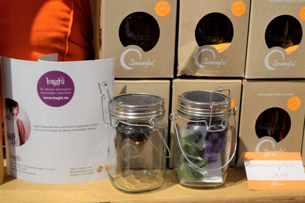 Produkte: Yogakissen im Hintergrund, Sonnengläser im Regal des Weltladen Marburg