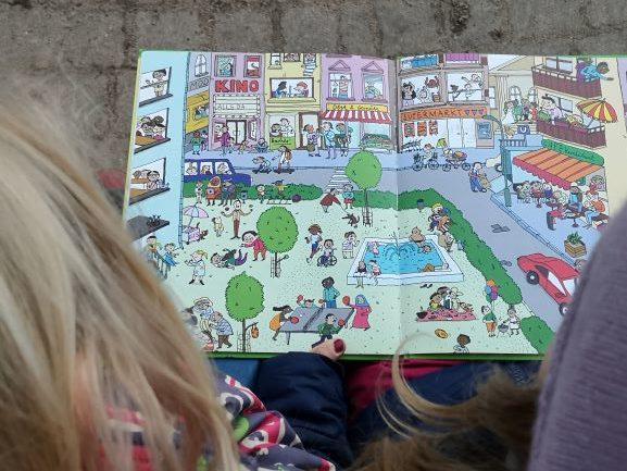 Kinder schauen ein Wimmelbuch an